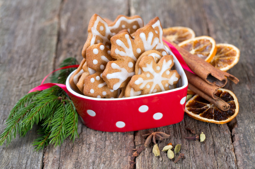 Decorated Christmas cookies in a beautiful red bowl on an old wooden background